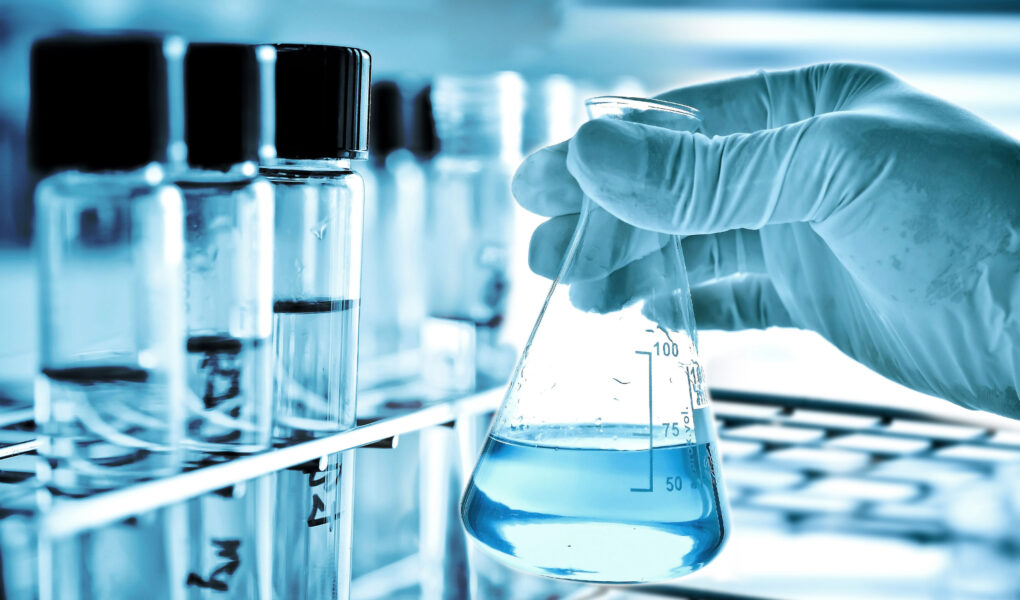 45720416 - flask in scientist hand and laboratory glassware background